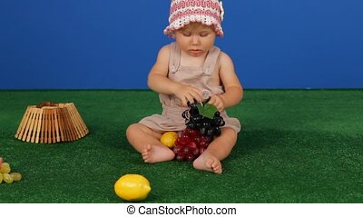 Girl And Grapes - Little girl sitting on the grass and...