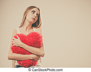 Sad unhappy woman holding red heart pillow - Broken heart...