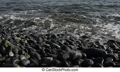 Small Waves on Rocky Beach - Small waves wash over a smooth...