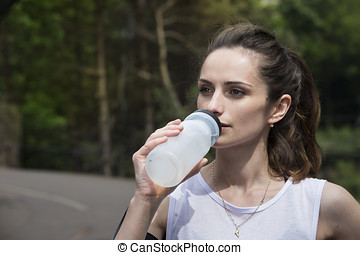 Athletic woman drinking water outdoors. - Athletic woman...