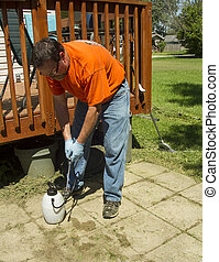 Worker Spraying Weed Killer On A Customers Patio