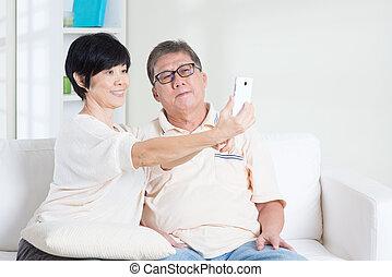 Senior using smart phone making selfie - Modern technology,...