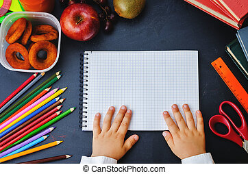 childrens hands holding notebook on a blackboard school...