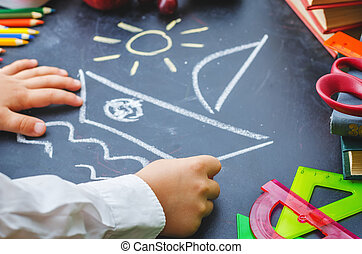childrens hands writing on a blackboard. school concept. the...