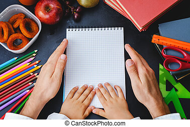 Mens and childrens hands holding a notebook School concept...
