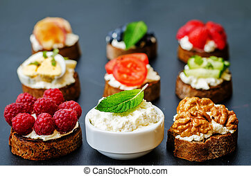 ricotta and crostini appetizers with fillings on a black...