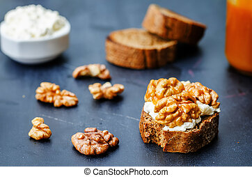 crostini with walnuts and caramel on a black background the...