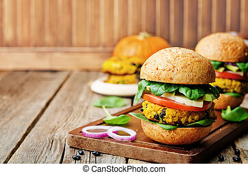 vegan millet black bean pumpkin burgers on a dark wood...