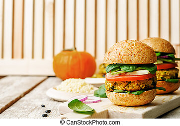 vegan millet black bean pumpkin burgers on a white wood...