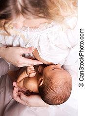 Breastfeeding. Mother feeding six month baby girl.