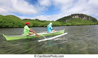 Ride on the outrigger canoe - Young woman took a guided ride...