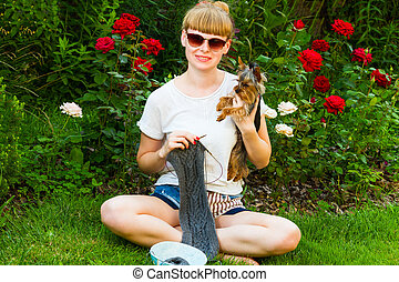 young wooman with needlework and dog in garden