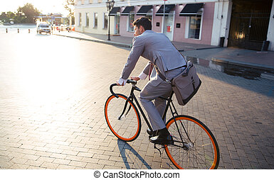 Businessman riding bicycle to work on urban street in...