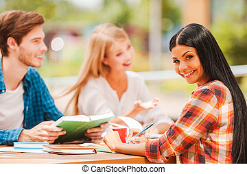 Enjoying campus life. Cheerful young woman holding pen and looking at camera while sitting with her friends at the wooden desk outdoors