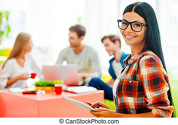 Creativity is in the air. Cheerful young woman working on digital tablet and looking at camera while her colleagues working in the background
