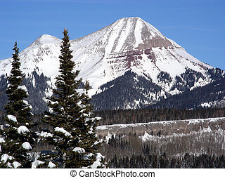 Emergence - Snow capped high mountain peak during winter in...
