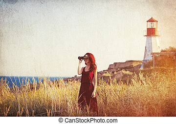 girl with binocular near Lighthouse - young redhead girl...