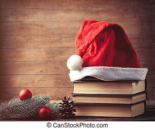 Santas hat and pine brench with books on wooden table
