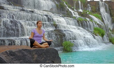 Meditating - Young woman meditating at the waterfall
