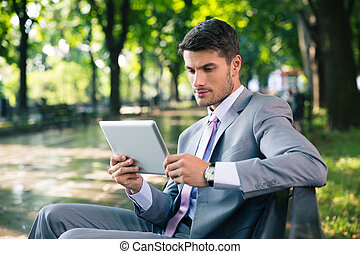 Businessman using tablet computer outdoors - handsome...