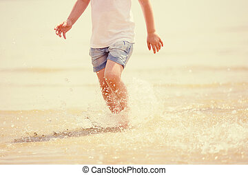 Child running beach shore splashing water, tinted photo