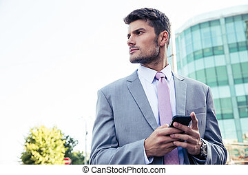 BUsinessman using smartphone ourdoors - Bsinessman using...