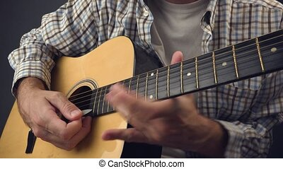 Playing solo on acoustic guitar - Man playing solo rock tune...