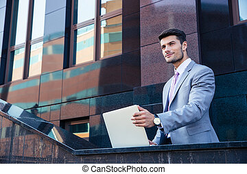 Businessman with laptop outdoors - Smiling handsome...