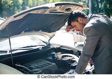 Man looking under the hood of car - Young man looking under...