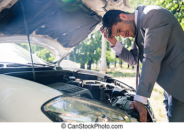 Man looking under the hood of car - Man in suit looking...