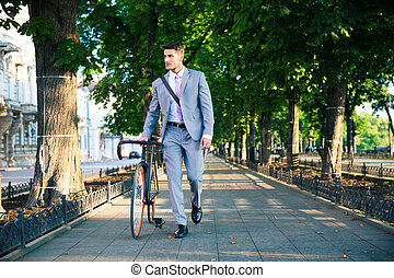 Businessman walking with bicycle - Handsome businessman...