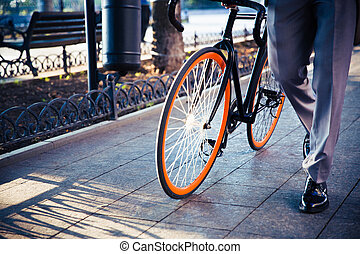 Businessman walking with bicycle - Closeup portrait of a...