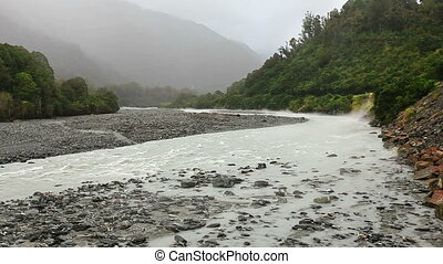 Misty stream running from glacier under rainfall. South...