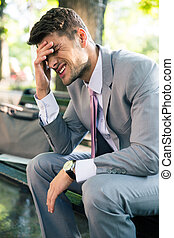 Depressed businessman sitting on the bench