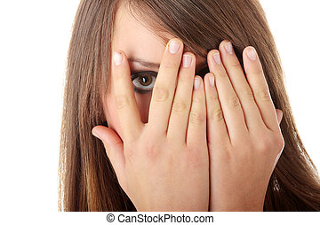 Frightened girl hiding her face behind her hands isolated on...