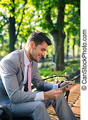 Businessman using tablet computer outdoors - Smiling young...