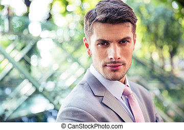 Portrait of a handsome businessman outdoors looking at...