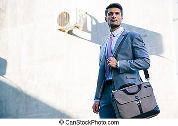 Portrait of a confident businessman standing outdoors near...