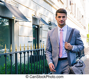 Portrait of a handsome young businessman walking in the city