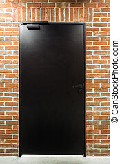 Modern black door in a brick wall - Illuminated modern black...