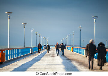 People walking on the pier in the winter.