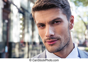 Closeup portrait of a handsome businessman outdoors looking...