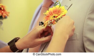 Attaching Boutonniere - Womens hands are inserted into the...