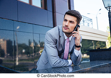 Businessman talking on the phone outdoors - Thoughtful...
