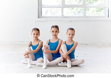 Three little ballet girls sitting and posing together -...