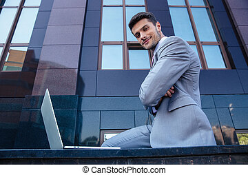 Businessman with laptop outdoors - Portrait of a happy...