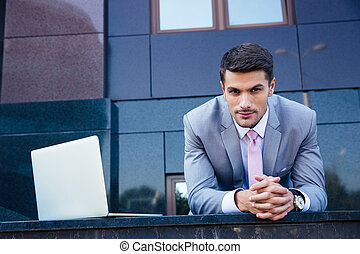 Businessman with laptop outdoors - Portrait of a confident...