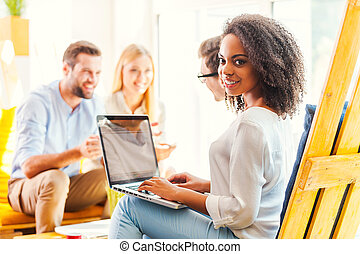 Working in a creative environment. Smiling young African woman working on laptop while her colleagues discussing something in the background