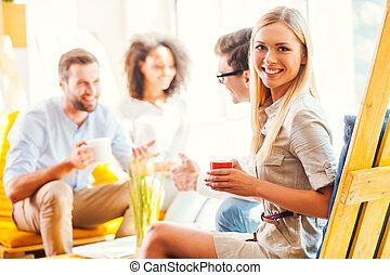 Happy to be a part of successful team. Happy young woman holding cup of coffee and looking at camera while her colleagues discussing something in the background
