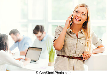 Keeping in touch with clients. Cheerful young woman talking...